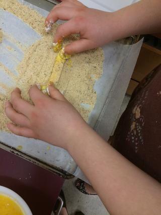 Enrolle el trozo de queso en el pan rallado sobre el papel encerado.