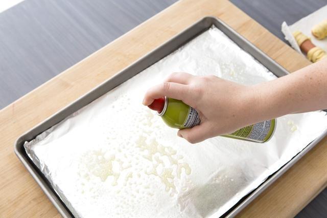 Coloque una hoja de papel en una bandeja de horno y rociar con aceite en aerosol para evitar que las momias de perros calientes se pegue.