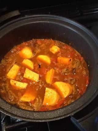 Añadir la lata de tomates y el camote y añadir agua suficiente para cubrirlos, llevar a ebullición. Cubra con una tapa y cocine a fuego lento durante unos 30 minutos