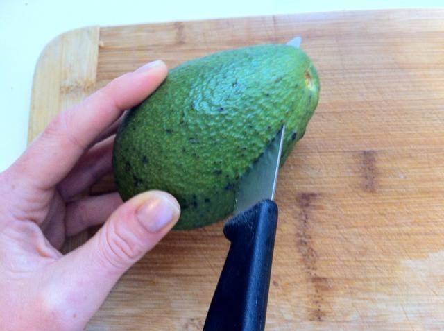 Siga el cuchillo alrededor de la piedra. Luego torcer las 2 mitades.