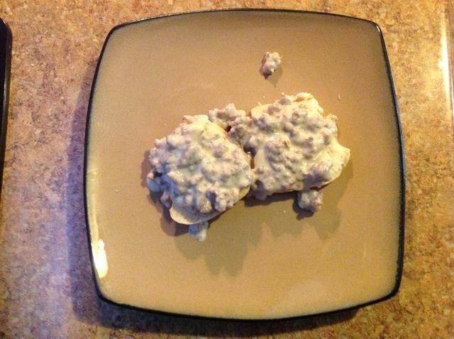Divida una galleta por la mitad en un plato y la parte superior de cada mitad con una deliciosa salsa de salchichas. Ahora estás listo para disfrutar de la mejor comida casera sur