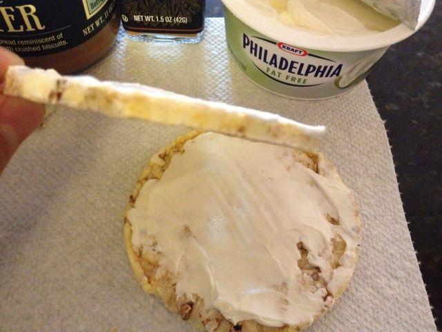 Extender una media onza (aproximadamente 1 cucharada) de la crema de queso sobre cada torta de maíz. Sea muy cuidadoso como las tortas de maíz son muy delgadas y frágiles en comparación con las tortas de arroz regulares.