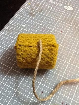 A continuación, poner una pequeña gota de pegamento caliente donde el tejido fin de mes y pulse el yute en la cola.