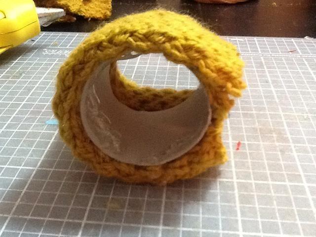 Ahora que el tejido está pegado a la tirada, usted va a poner un círculo de pegamento caliente en cada lado y presione la tela adicional en el interior del núcleo.