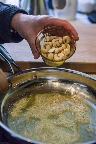 Cuando la mantequilla de espuma y empieza a aclarar, echar en el anacardo o trozos de almendra.