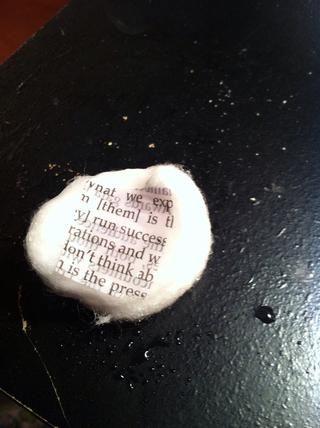 Ponga un cuadrado de papel de periódico en una bola de algodón húmedo