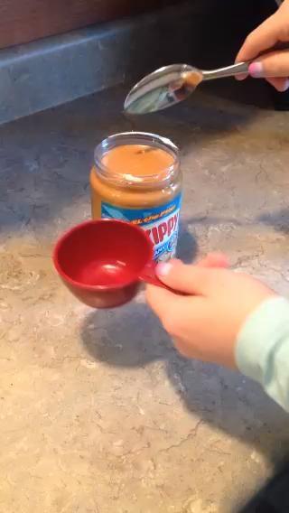 Vierta la mitad de una taza de mantequilla de maní en la taza de medir. Añadir a la taza.