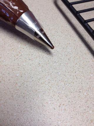 Ablande Nutella en el microondas durante unos 10 segundos y luego poner la Nutella en una manga pastelera con una punta número uno o dos de decoración