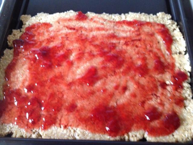 Ponga 3/4 de la mezcla en una fuente de horno greesed y plano hacia abajo la mezcla. Fundir el limón y mermelada en el microondas y se extendió sobre la mezcla aplanado