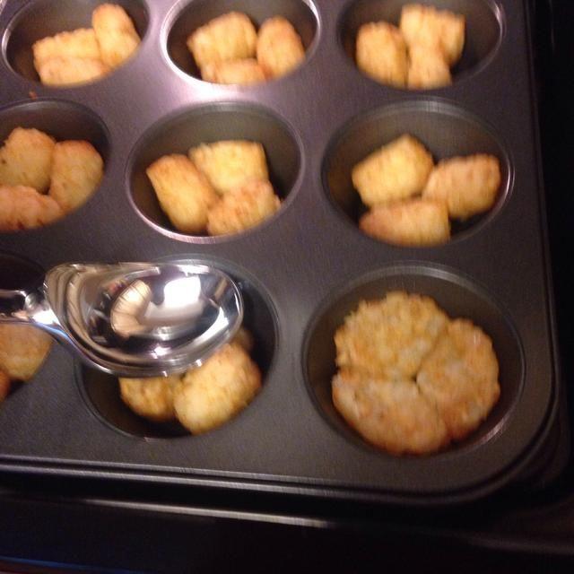 Retire la sartén del horno y presione los pequeñitos tater hacia abajo para formar una base con la parte posterior de una bola de helado o una taza de medir.