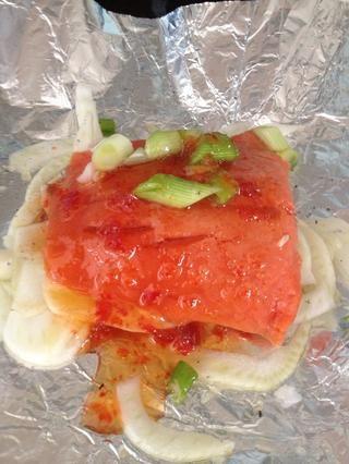 Coloque filete de salmón en la parte superior del hinojo. Apriete en un poco de limón. Rocíe en el sésamo y teriyaki. Dispersión de cebollas de primavera en la parte superior. Verter sobre la salsa de chile dulce (Mi favorito es el de las granjas Riverford)