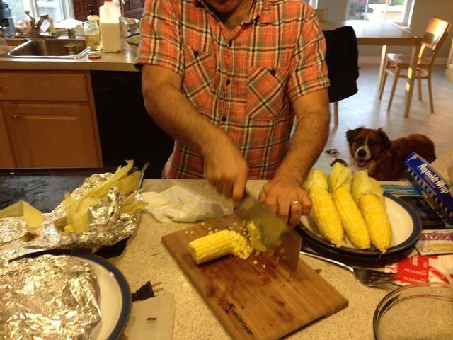 Echa un vistazo por encima al marido cortando maíz para asar a la parrilla ... Mira el perro viendo toda la acción!