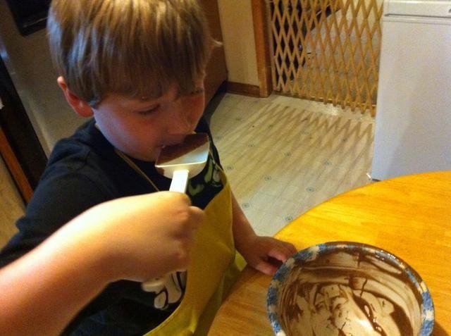 Querido hijo teniendo un gusto. Le encanta ayudar a cocinar.