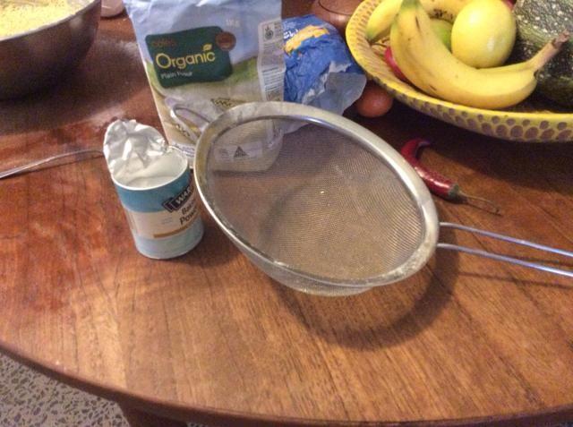 Siguiente tamizar la harina y la levadura en la mezcla de huevo y mantequilla.