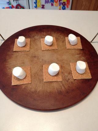 Romper las galletas graham en cuadrados y colocar en un molde para hornear. Coloque una gran malvavisco en la parte superior de cada galleta.