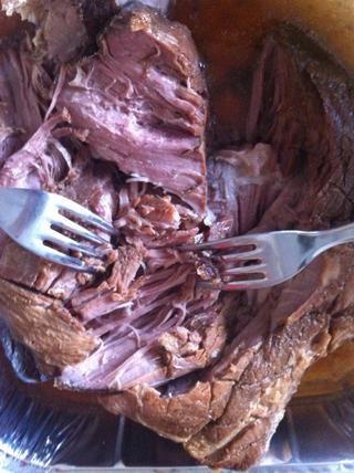 Con dos tenedores, tire suavemente aparte la carne de cerdo tierno. Debe haber un montón de jugos en la sartén para que se mezcle con. Continúe hasta que se tritura toda la carne de cerdo.