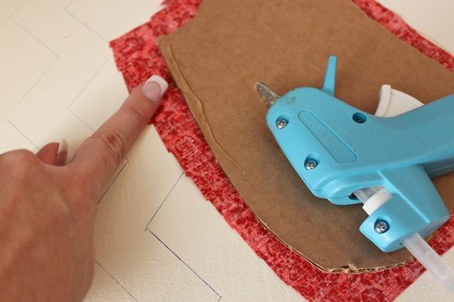 Añadir un poco de pegamento caliente en el borde de su cartón. Doble la tela sobre instalarla en el cartón en todos los lados.