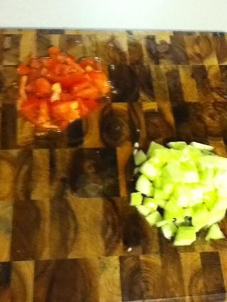 Ahora deja's do the salad, dude. Chop a tomato and half a peeled cucumber. Squeeze the water out...