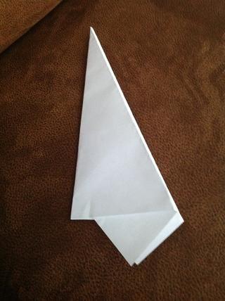 Gire el avión de papel y dobla por la mitad a lo largo de la línea central.
