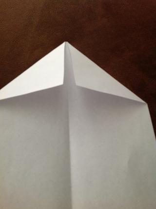 Abra el avión de papel hacia arriba. Doble cada esquina hacia el centro hasta el punto donde los bordes interiores son incluso con el pliegue central.