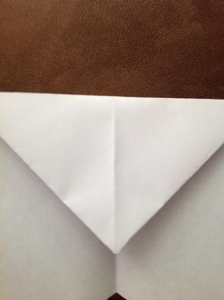 El borde inferior de las esquinas que acaba de abatirse debe crear una línea recta a través de la página. Dobla hacia abajo en esta línea.