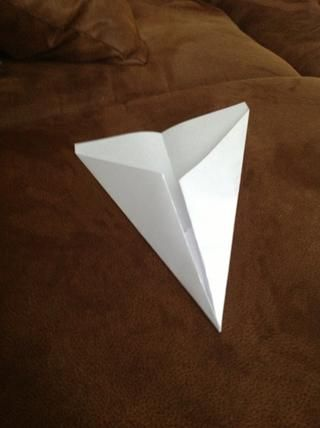 Comenzando en la punta de la punta, doble el papel hacia abajo en cada lado por lo que los bordes interiores se alinean con el pliegue central.
