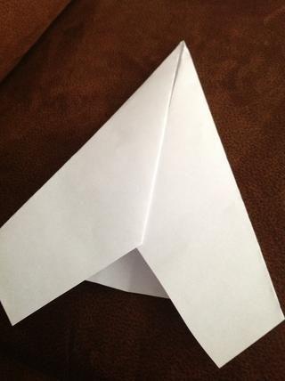 Comenzando en la punta de la punta, doble el papel por encima de cada lado por lo que los bordes interiores se alinean con el pliegue central.