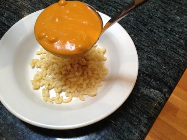 Cuchara con cuidado la base de garbanzo de tomate en la parte superior de la pasta de manera que no hay salpicaduras en el lado de la taza.