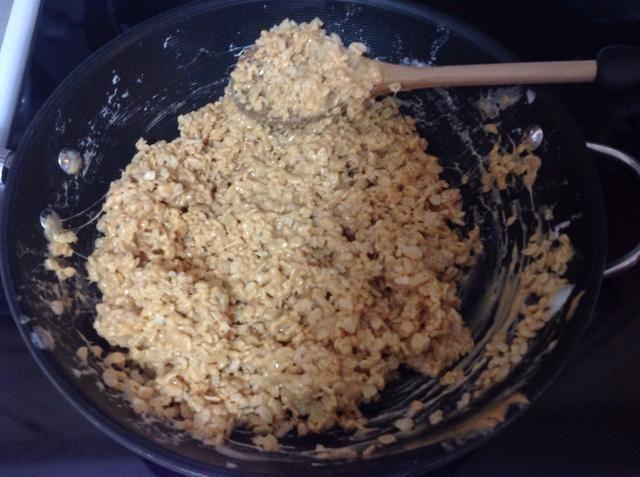Revuelva hasta que todos los Rice Krispies se recubren en la mezcla de malvavisco mantequilla de maní.