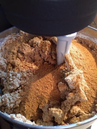 Añadir migas de galleta y cacahuates granulados.