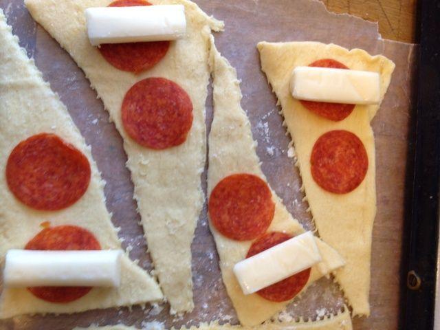 Tome la mitad de un palo de queso y un par de piezas de pepperoni y las ponen sobre el rollo de media luna.