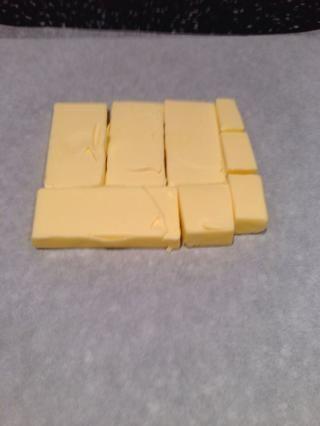 Cortar la mantequilla fría de la nevera en 1.25cm losas. Colóquelos en papel encerado para formar un cuadrado de unos 15x15cm. Cubra con papel encerado y más libras con un rodillo hasta que's 19x19cm