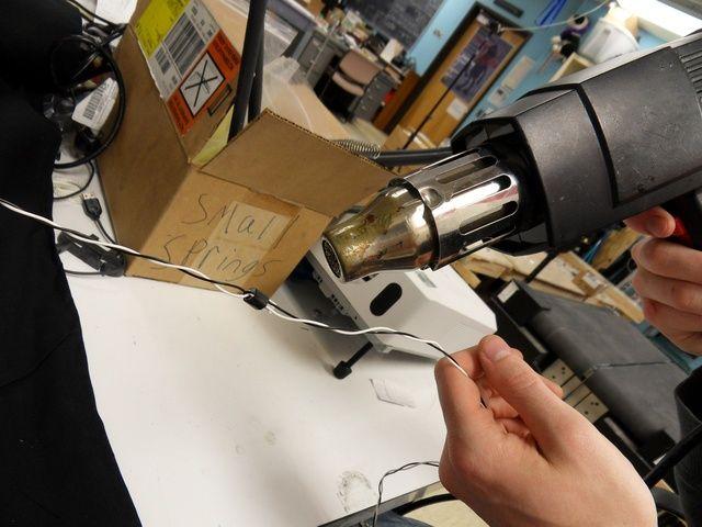 Mantenga pulsado los cables firmemente y utilizar la pistola de calor para asegurar el encogimiento del calor a su alrededor.