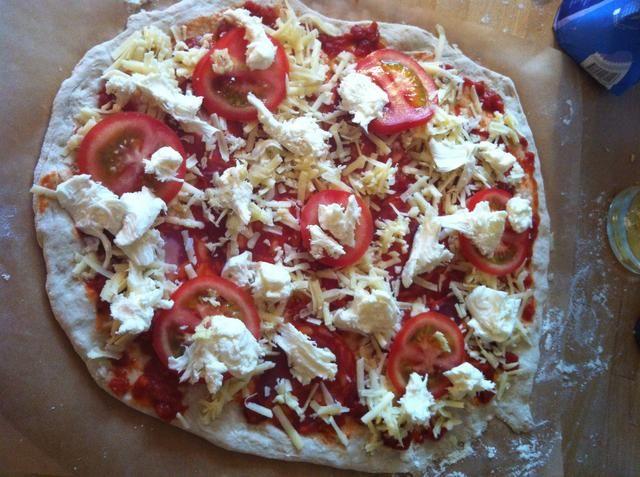 Éste tiene la salsa de tomate, pepperoni, queso, ajo, tomate y mozzarella de búfala. Tenga en cuenta el papel de horno bajo el pastel listo para deslizarse sobre una tabla de cortar.