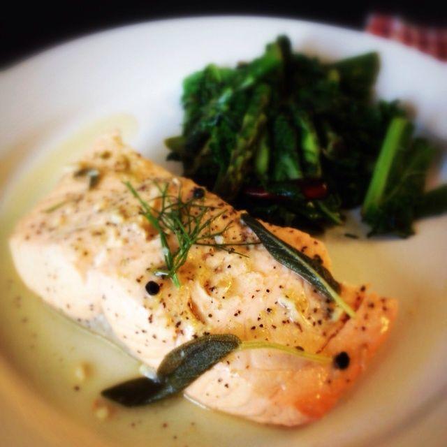 Saque el pescado del líquido. Continuar la ebullición del líquido y sazonar con sal y pimienta. Vierta sobre el pescado. Servido con verduras salteadas (muestra: espárragos y col rizada)