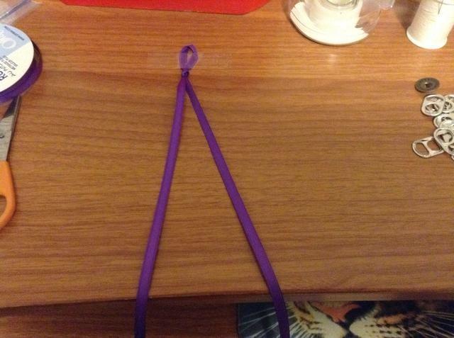Haga un nudo de lazo en medio de su cinta. Luego, la cinta a una mesa. (Esto hace que los próximos pasos mucho más fácil)