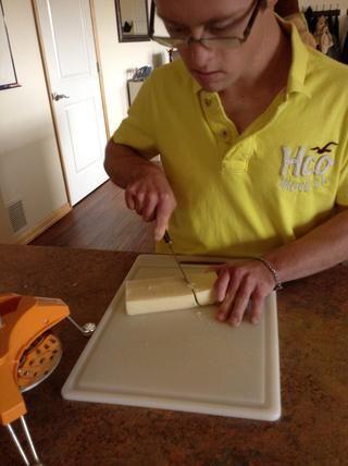 Usando el cuchillo y la tabla de cortar cortar el queso en pequeños cuadrados.