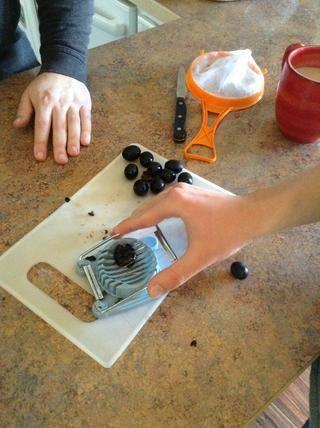 El uso de una máquina de cortar del huevo puesto 1 de oliva a la vez en la base y presione el mango hacia abajo. Esto cortar las aceitunas