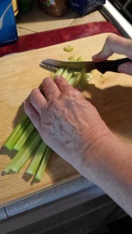 A continuación, obtener 2 existencias de apio y cortarlos por la mitad, la mitad otra vez, y luego en trozos pequeños y agregarlos a la taza.