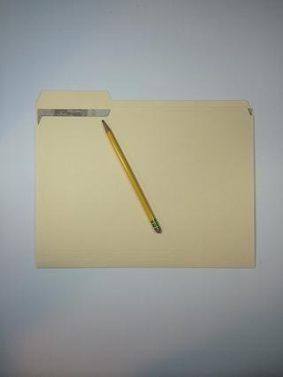 Coloque la pieza más grande dentro de una carpeta de manila (debe haber espacio en el borde izquierdo y derecho) y trace el borde superior con un lápiz.