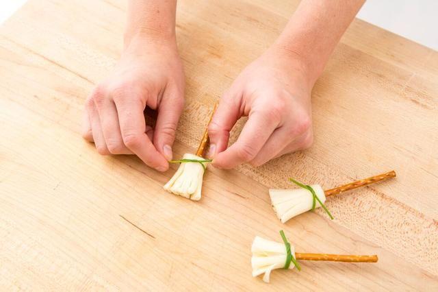 Encuentra las cebolletas más delgados en su contenedor y lo atan alrededor del queso.