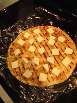 Cortar el queso en cuadrados en todo el pizza. No tan cerca del lado porque va a supurar terminado. Utilice la mozzarella envasados no el húmedo en salmuera.