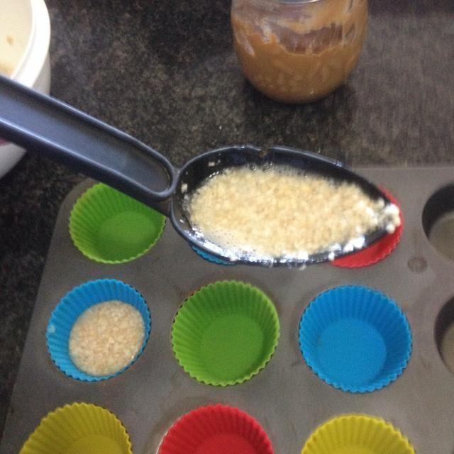 Line La lata de la magdalena con las tazas de la hornada. A continuación, utilice una cuchara grande para llenar las copas con la mezcla.
