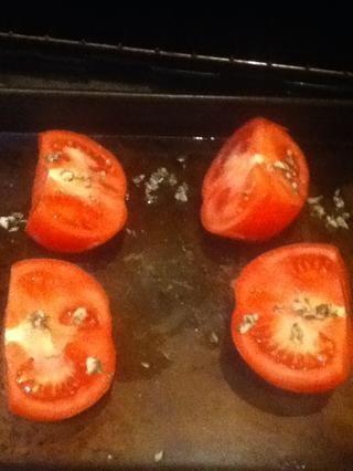 Ponga los tomates cortados lados en una pequeña fuente de horno engrasada y rociar con un tercio de la mezcla de ajo. Ase hasta que estén tiernos, de 30 a 40 minutos.