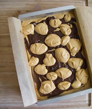 Corre otra mitad de la masa de brownie sobre el cheesecake. Masa masa restante de queso sobre la mezcla de brownie.