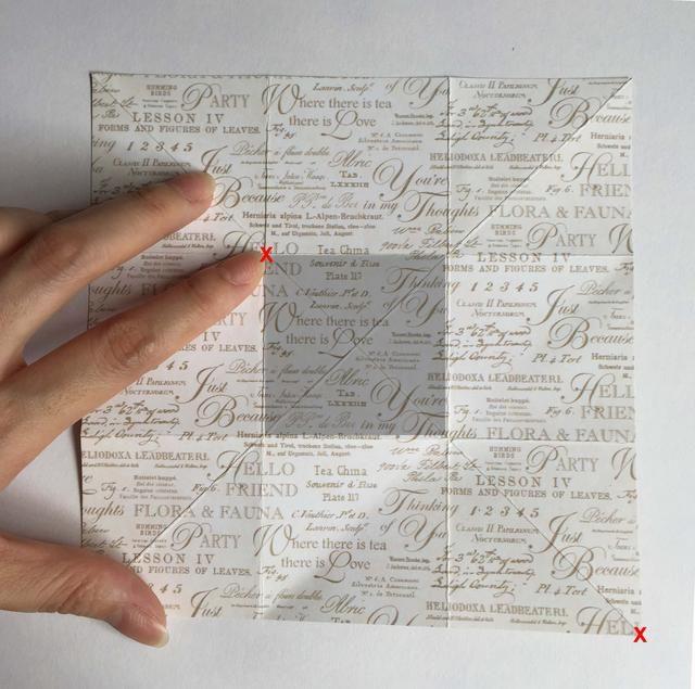 Doblar diagonalmente a través de la esquina inferior derecha del papel (x roja) en dirección a donde mi dedo índice (rojo x) está apuntando en la esquina superior izquierda de la caja gris con sombra ...