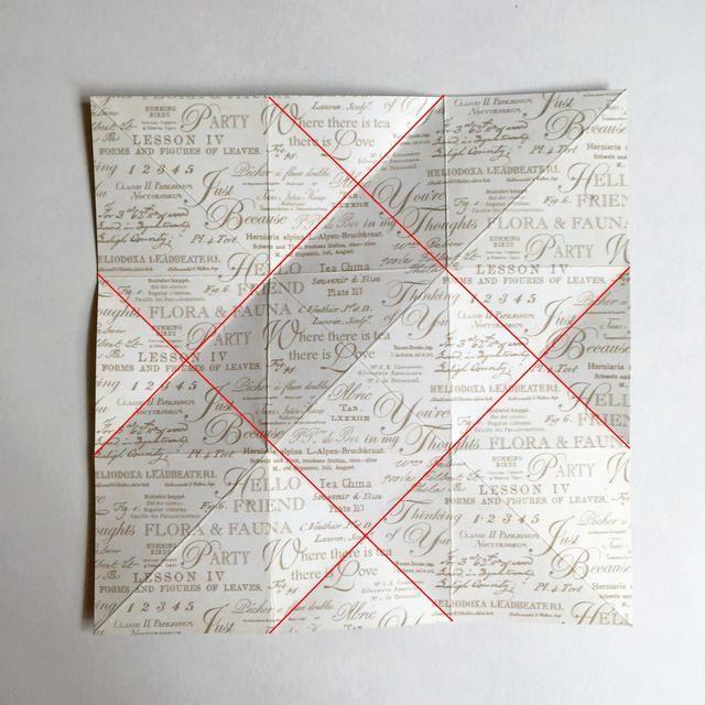 A medida que desdobla el papel, obtendrá 4 pliegues diagonales a través del papel, como se indica por las líneas rojas aquí ...