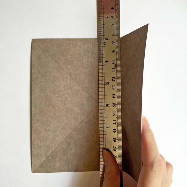 Utilizando una regla de metal como guía, doblar los papeles en consecuencia ... Usted debe tener 2 líneas dobladas con 3 columnas ...
