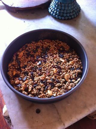Agregue la taza de buckinis (o muesli tostado) al bol con el aceite de coco derretido y revolver hasta que's all coated with the oil. Then tightly press the mixture into a tin.