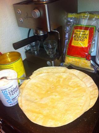 Configure su estación de fomento enchilada: apoderarse de su queso rallado, crema agria, tortillas de harina, y la salsa de enchilada. Tener el pollo preparado cerca.